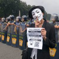 No-go: An Anonymous protester wearing a Guy Fawkes mask is blocked by riot police during a rally calling for Internet freedom held in Manila last November. | AFP-JIJI