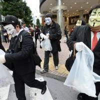 Subversion: Members of the hacker collective Anonymous wear Guy Fawkes masks during a clean-up mission in Tokyo on Monday. | AFP-JIJI