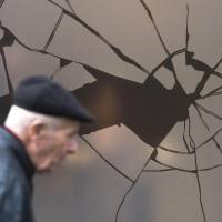 In remembrance: A man walks past a storefront with a sticker simulating broken glass at a department store in the German capital Friday, ahead of the 75th anniversary of the Nazis' Kristallnacht (Night of Broken Glass) anti-Jewish pogrom of Nov. 9-10 1938. | AFP-JIJI