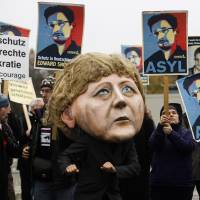 Getting a big head?: A demonstrator with a mask depicting German Chancellor Angela Merkel  poses  in front of other protesters holding posters of former National Security Agency contractor Edward Snowden outside the German parliament building prior to a special meeting of lawmakers on the U.S.-German relationship, in Berlin on Monday. Posters read 'Shelter for Edward Snowden in Germany,' and 'Asylum.' | AP