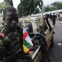 Too young: A child soldier fighting with Seleka rebels sits on a pickup truck near the presidential palace in Bangui, the capital of the Central African Republic, in March. | AFP-JIJI