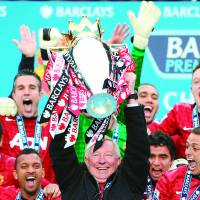 Out in a blaze of glory: Retiring Manchester United manager Alex Ferguson lifts the trophy as he and his team celebrate the 13th Premier League title of his 26-year tenure at Old Trafford. | AFP-JIJI
