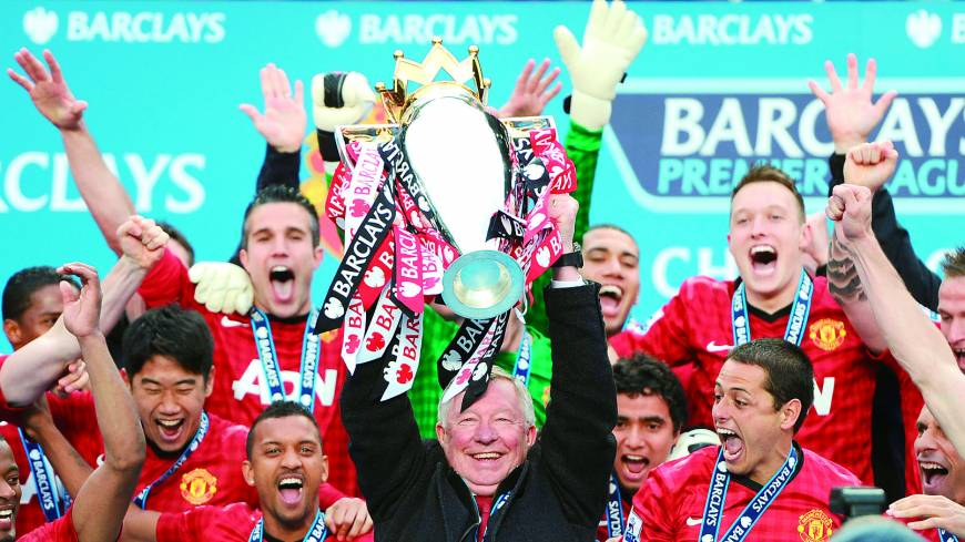Out in a blaze of glory: Retiring Manchester United manager Alex Ferguson lifts the trophy as he and his team celebrate the 13th Premier League title of his 26-year tenure at Old Trafford.