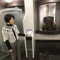 High-tech cemetery: Nichiryoku Co. employee Junko Tsuruno uses a card reader to open a booth containing a tombstone in Daitokuin, a high-tech temple in Tokyo. | AP