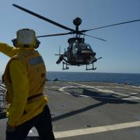 A tossing LZ: A U.S. Army OH-58 Kiowa Warrior helicopter lands on the guided missile cruiser USS Lake Erie on Dec. 9. | THE WASHINGTON POST