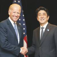 Trans-Pacific friends: U.S. Vice President Joe Biden and Prime Minister Shinzo Abe shake hands for the cameras before holding a meeting in Singapore in July. | KYODO