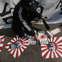 Graphic display: A protester lays out copies of Japan's naval ensign with images of Prime Minister Shinzo Abe and wartime Prime Minister Gen. Hideki Tojo in Hong Kong on Friday. | AP
