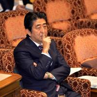 Hush now: Prime Minister Shinzo Abe tells opposition lawmakers to be quiet at a session of the Upper House committee on national security Wednesday. | AFP