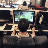 Hooked: A college student plays online games at an Internet cafe in Seoul on Wednesday. A law under consideration in parliament has sparked debate by grouping online games as an anti-social addiction alongside gambling, drugs and alcohol. | AP