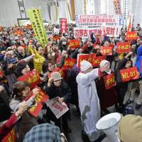 Seeing red: Activists rally Friday at Okinawa's prefectural government offices against a plan to build a new U.S. Marine base in Nago. | KYODO