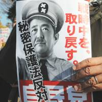 It can't happen here: A man protesting the contentious state secrecy bill outside the Diet building Thursday holds up a doctored photo that depicts Prime Minister Shinzo Abe as the title character in Charlie Chaplin's classic movie 'The Great Dictator' with the phrase 'I'll take Japan back to the time of war.' | SATOKO KAWASAKI