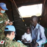 Extra duties: Ground Self-Defense Force members of a U.N. peacekeeping operation in South Sudan examine a refugee parent and his child Sunday in Juba. | KYODO