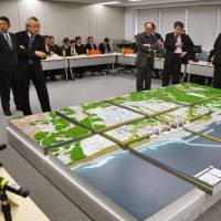 Big mess in miniature: A panel consisting of experts and Tokyo Electric Power Co. and government officials view a model of the Fukushima No. 1 plant and groundwater flows Tuesday at the Ministry of Economy, Trade and Industry. | KYODO
