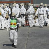 Hazmat-only: Workers mass near the reactor 4 building at Tokyo Electric Power Co.'s Fukushima No.1 nuclear power plant in March. | BLOOMBERG
