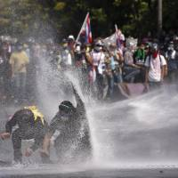 Hosed: Anti-government protesters shield themselves against a water cannon sprayed by police in Bangkok on Monday. | AP