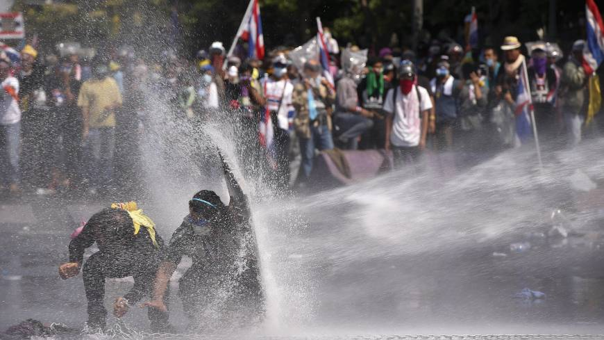 Hosed: Anti-government protesters shield themselves against a water cannon sprayed by police in Bangkok on Monday.