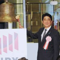 Stakeholders: Prime Minister Shinzo Abe rings the bell Monday to mark the end of 2013 trading on the Tokyo Stock Exchange as Paralympian Mami Sato, who contributed to the successful bid to host the 2020 Olympics in Tokyo, looks on. | SATOKO KAWASAKI