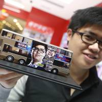 Big wheel: Tony Chow shows his self-advertising plan using a model of a Hong Kong double-decker bus with his face plastered on the sides.  | AP