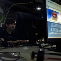 Casting a wide Net: A monitor set up in a Beijing Internet cafe in August displays a message from Chinese police on the proper Internet use. | AP