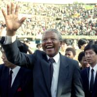 Memories of Madiba: Nelson Mandela is welcomed by supporters during a visit to Osaka in October 1990. The former South African president and anti-apartheid icon died Thursday at age 95. | KYODO