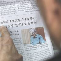 Clipped: An ex-member of the Kuwol unit reads a report in Seoul on Monday of Merrill Newman's detention in North Korea. | AP