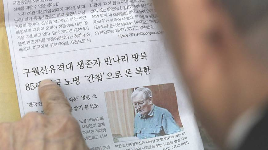 Clipped: An ex-member of the Kuwol unit reads a report in Seoul on Monday of Merrill Newman's detention in North Korea.