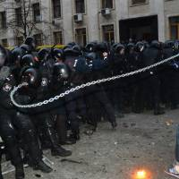Unchained: A protester whips a chain at police while attempting to storm the offices of Ukrainian President Viktor Yanukovych in Kiev during a mass rally Sunday. | AFP-JIJI