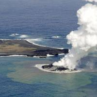 Expanding: A new volcanic island is shown on Nov. 21, a day after emerging about 1,000 km south of Tokyo. Right: It is nearly twice as big Friday afternoon. | KYODO