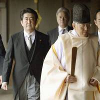 Treading contentious waters: Led by a shinto priest, Prime Minister Shinzo Abe walks in the corridor at the main building of Yasukuni Shrine in Tokyo on Thursday. | KYODO