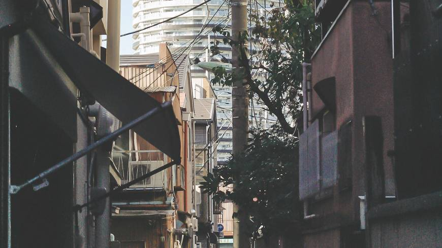 One of Kyojima's many narrow streets lies in the shadow of an apartment block built in the neighboring Hikifune district.