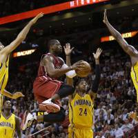 Stuck in no man's land: Heat guard Dwyane Wade tries to get a shot up against the Pacers defense on Wednesday in Miami. Wade scored a game-high 32 points in the Heat's 97-94 victory. | AP
