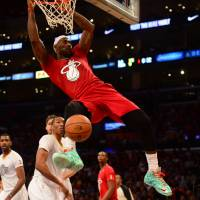 Deck the halls: Heat forward LeBron James dunks against the Lakers during their matchup on Christmas Day in Los Angeles. Miami held on late to win 101-95. | AFP-JIJI