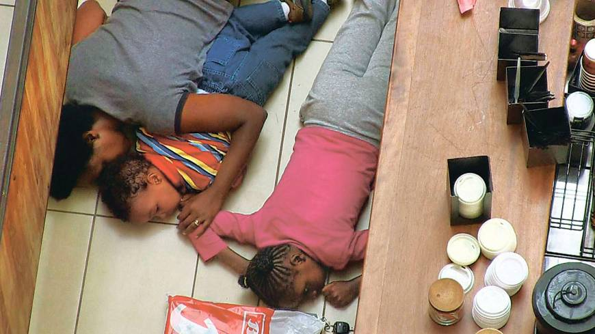 Take cover: A woman and two children hide behind a bar in Nairobi's upscale Westgate Mall during an attack by gunmen linked to the Somali terrorist group al-Shabab on Sept. 21.