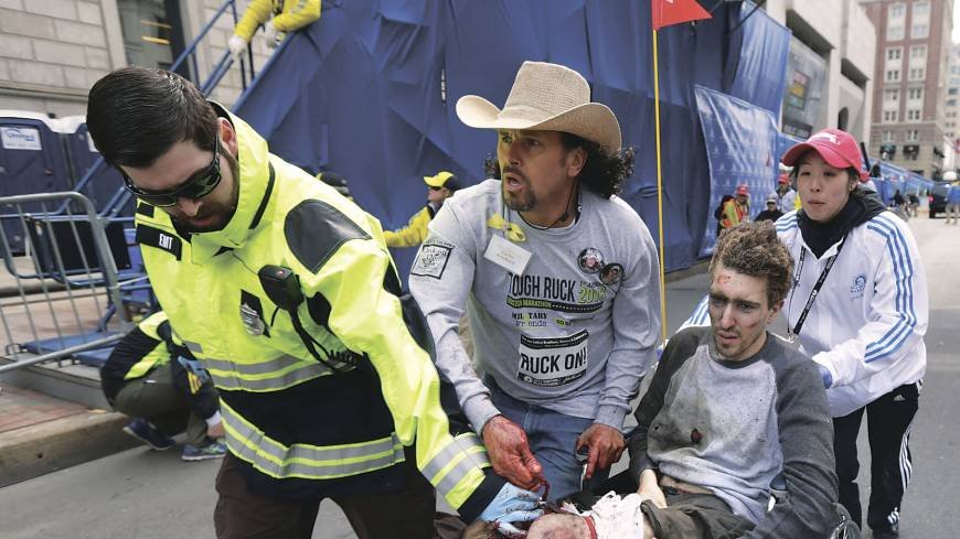 Run to safety: An emergency responder and volunteers, including Costa Rican-American peace activist and Red Cross volunteer Carlos Arredondo (center), push victim Jeff Bauman in a wheelchair after he was wounded by the Boston Marathon bombings on April 15.