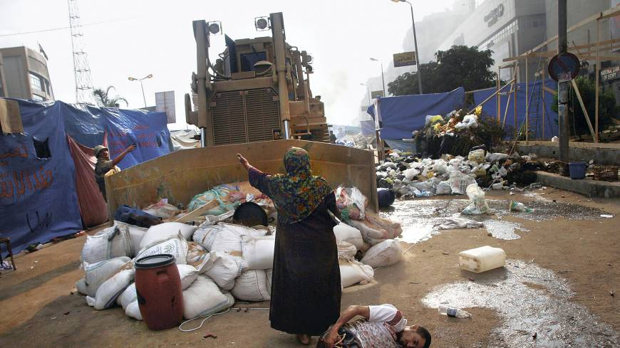 Full stop: An Egyptian woman tries to prevent a military bulldozer from hurting an injured youth during action against supporters of deposed President Mohammed Morsi at a protesters' camp in Cairo on Aug. 14.