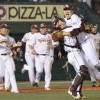 Tohoku Rakuten catcher Motohiro Shima lifts pitcher Masahiro Tanaka after clinching the Golden Eagles' first Japan Series title against the Yomiuri Giants in Sendai in November.  | KYODO