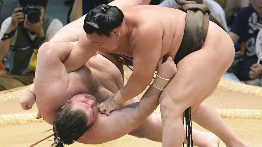 King of the castle: Hakuho throws Gagamaru to the ground at the Nagoya Grand Sumo Tournament in July.