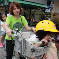 Infraction!: A Japanese mother wantonly breaks the law by carrying more than one child on her deadly treadly. | BLOOMBERG