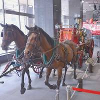 Putting the cart behind the horse: A child admires one of Tokyo's earliest fire engines.