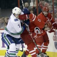 Got your nose: The Hurricanes' Eric Staal (right) competes for the puck against the Canucks' David Booth on Sunday. | AP