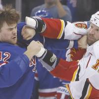 It's getting hot in here: The Flames' Brian McGrattan (right) lands a punch on the Rangers' Dylan McIlrath during their game on Sunday in New York. | AP