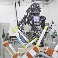 Warning! Warning!: A robot developed by Lockheed Martin clears a path through debris during a practice session for a robot competition. | AP