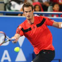 Back in action: Andy Murray plays a shot from Jo-Wilfried Tsonga in their match at the Mudabala World Tennis Championship in Abu Dhabi on Thursday. Tsonga won 7-5, 6-3. | AFP-JIJI