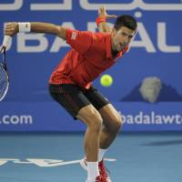 Backhand slice: Novak Djokovic plays a shot from David Ferrer in the final of the Mubadala World Tennis Championship on Saturday. | AP