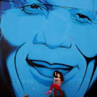 Face of a nation: Two girls are seen beneath a wall mural of former South African President Nelson Mandela in Cape Town on Dec. 7. | AP