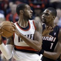 Playing both ends: Miami's Chris Bosh defends against Portland's LaMarcus Aldridge in the first half on Saturday night. | AP