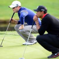 What are we looking at?: Zach Johnson (left) and Tiger Woods line up their putts during their World Challenge match on Sunday in Thousand Oaks, California. | AP