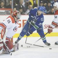 Hacked: Vancouver's Daniel Sedin has his stick broken by Carolina's Jay Harrison as Hurricanes goalie Justin Peters looks on Monday. The Canucks defeated the Hurricanes 2-0. | AP