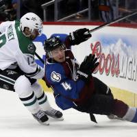 Falling down: Colorado's Tyson Barrie slides into the boards as Dallas' Ray Whitney looks on in the third period on Monday night. | AP