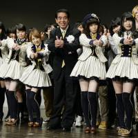 Pop culture: Education minister Hakubun Shimomura poses with idol group AKB48 at Waseda University in Tokyo's Shinjuku Ward on Dec 15. | KYODO
